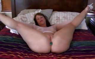 Horny brunette in lingerie and anal plug gets fingered in solo