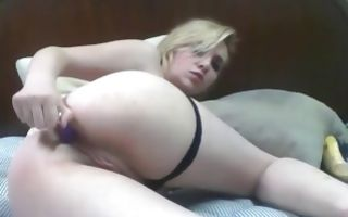 Nude blonde lying on her bed and fucking her vagina with a dildo